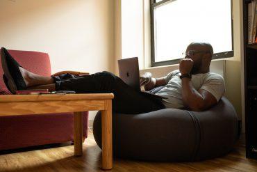 Skaldet mand sidder med sin computer